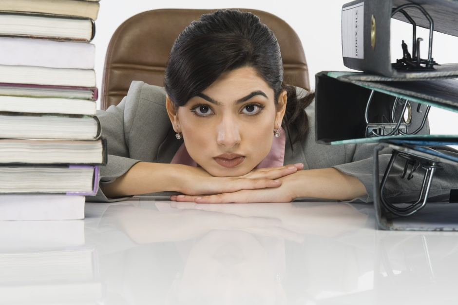 Stack of books and binders in front of a businesswoman at desk