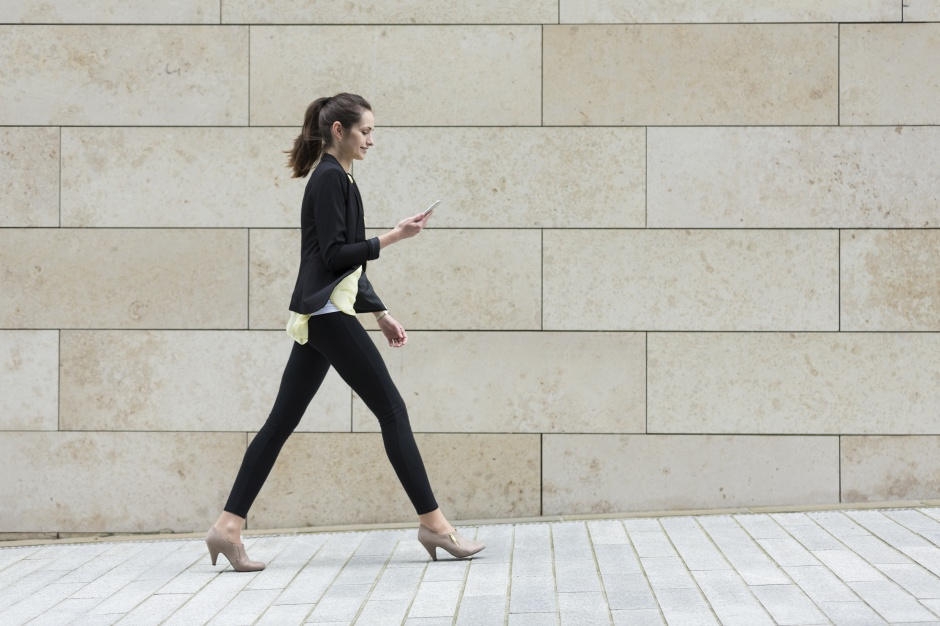 Businesswoman looking at phone while walking.