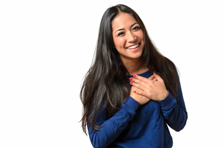 Young woman showing her heartfelt gratitude and thanks clasping her hands to her heart with a pleased smile