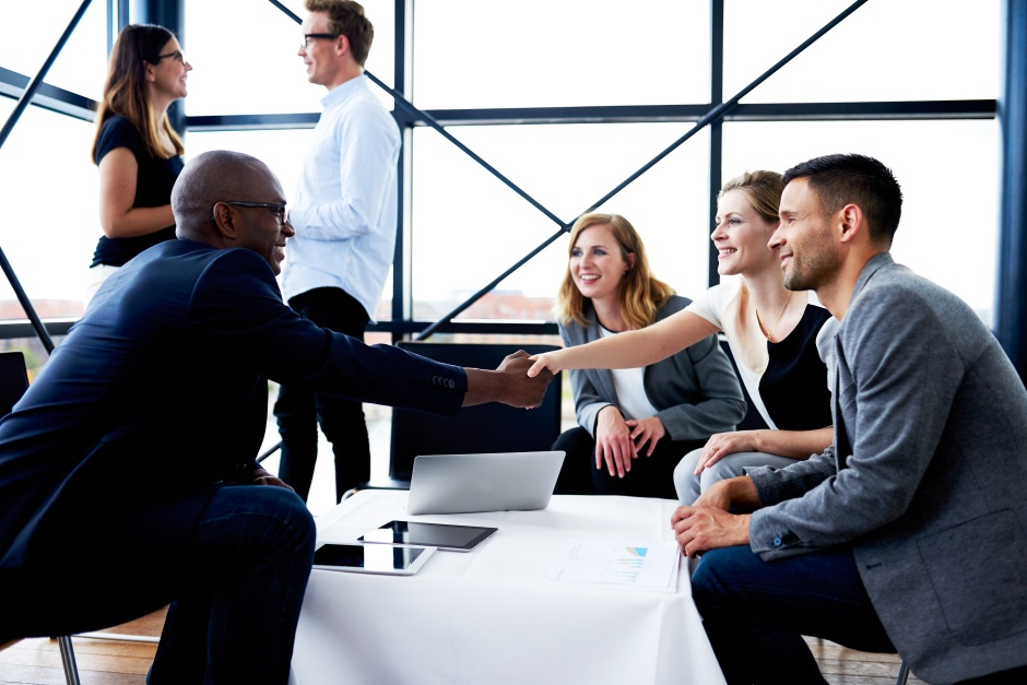 Black executive shaking hands with female colleague