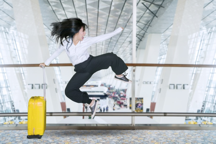 Happy businesswoman jumps in the airport
